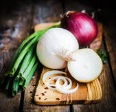 Colorful onions and garlic on rustic wooden background — Stock Photo