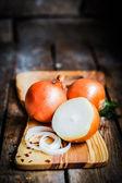 Colorido cebollas y ajo sobre fondo de madera rústica — Foto de Stock
