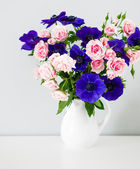 Bouquet of pink roses and blue anemones in white vase — Stock Photo
