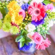 Colorful bouquet of spring flowers in vintage vase on rustic wooden background — Stock Photo #42805779