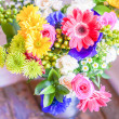 Colorful bouquet of spring flowers in vintage vase on rustic wooden background — Stock Photo