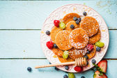 Pancakes with berries on wooden background — Stock Photo