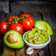 Guacamaole with bread and avocado on rustic wooden background — Stock Photo #43505533
