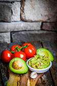 Guacamaole with bread and avocado on rustic wooden background — Stock Photo