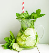 Water with limes and mint on wooden background — Stock Photo