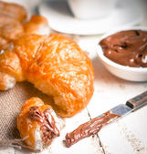 Fresh baked croissants with chocolate cream and hot cocoa — Stock Photo