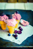 Ice -cream in cones with berries on rustic wooden background — Stock Photo