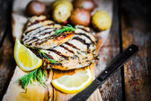 Grilled chicken with potatoes and asparagus on wooden background — Stock Photo