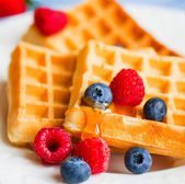 Belgian waffles with berries on rustic background — Stock Photo