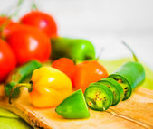 Assorted pepper and tomatoes on wooden background — Stock Photo