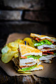 Club sandwich on rustic wooden background — Stock Photo