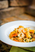 Italian pasta with shrimps and vegetables on wooden background — Stock Photo