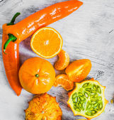 Orange fruits and vegetables on rustic background — Stock Photo