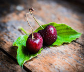 Cherries on rustic wooden background — Stock Photo