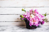 Peonies on rustic wooden background — Stock Photo