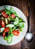 Vegetable salad on wooden background — Stock Photo