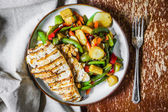 Grilled chicken with baked vegetables on rustic background — Stock Photo