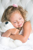 Cute baby girl with teddy bear in white bed — Stock Photo