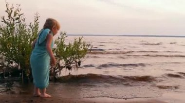 Little girl plays, looks afar at water — Stock Video