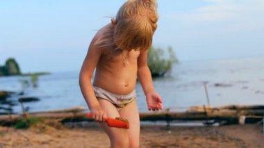 маленькая девочка играет, смотрит вдаль на воде — Стоковое видео