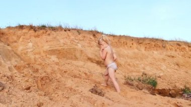 Little girl clambers on sand up, plays — Stock Video