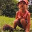Stock Video: Girl and hedgehog on grass