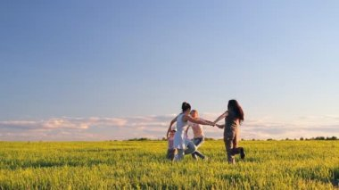 Two women and two children frolic, jump, whirl in a meadow on the green grass — Stock Video