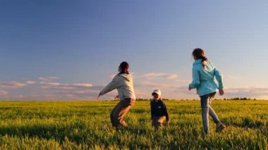 Women and two children frolic, jump, whirl in a meadow on the green grass — Stock Video