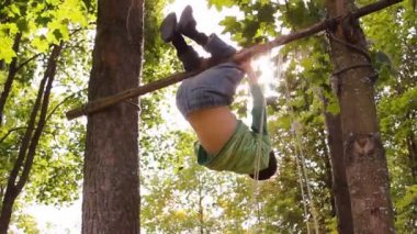 Boy somersaults on the bar, and climbs a tree — Stock Video