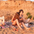 The mother and the two girls on the beach, a woman makes massage — Stock Video #34062973