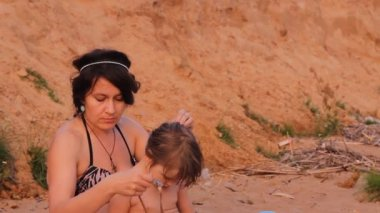 Mother brushed her hair daughter on the beach — Stock Video