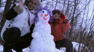 Woman (mother) and a little girl playing with snowman — 图库视频影像