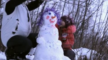 Woman (mother) and a little girl playing with snowman — Stockvideo