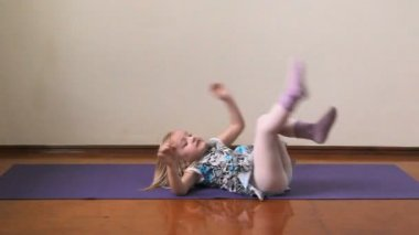 A little girl plays the fool, doing exercises, yoga — Stock Video