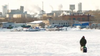Snowmobile rides on the background of factory chimneys and smoke — Stock Video
