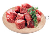 Raw fresh beef cubes on board with greens on white background — Stock Photo