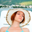 Stock Photo: Young female model lying down at sun lounger with beautifull lan
