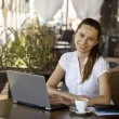 A young attractive business woman sitting in a cafe with a noteb — Stock Photo