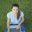 Young woman with laptop on green grass — Stock Photo #27613065