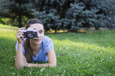 Young woman photographer portrait on the grass — Stock Photo
