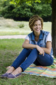 Young smilling woman in the park — Stock Photo