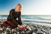 Blond Girl on the seaside hiding a heart — Stock Photo