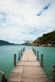 Wooden bridge with sea and the mountains — Stock Photo