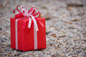 Red gift box on the rock — Stock Photo