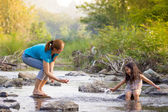 Asian mother and daughter playing water in the waterfall — Stock Photo
