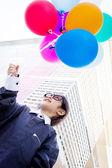 Cute little Asian business child holding balloon — Stock Photo