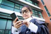 Cute little Asian business man using smartphone — Stock Photo
