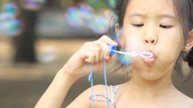 Little Asian child having fun making bubbles — Stock Video