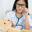 Asian girl playing as a doctor with stethoscope and bear doll — Stock Photo