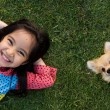 Happy Asian girl with her doggy portrait lying on lawn — Stock Photo #47940297